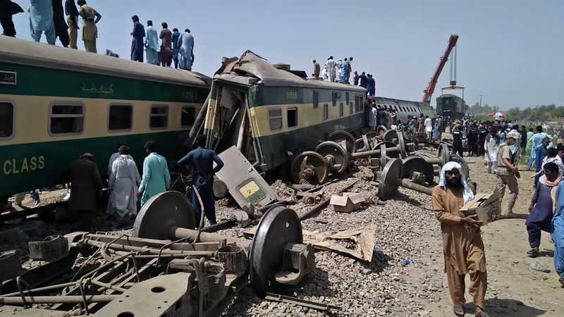 Soldiers and volunteers work at the site of a train collision in Ghotki district in southern...