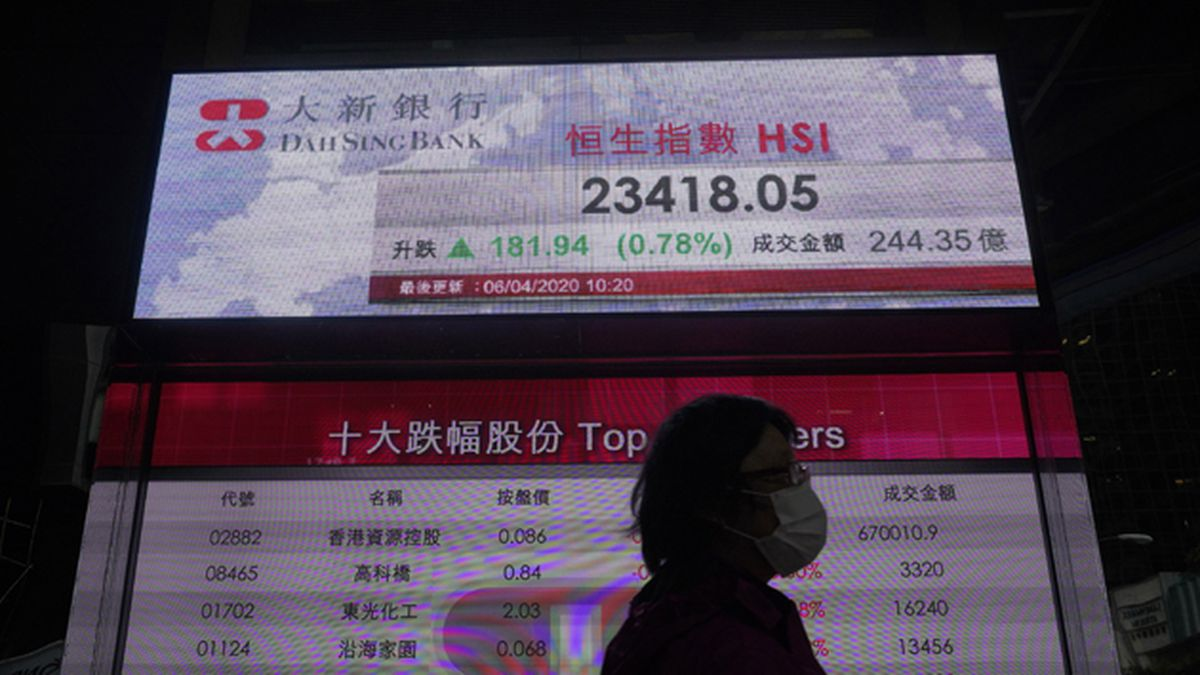 A woman wearing a face mask walks past a bank electronic board showing the Hong Kong share index in Hong Kong on Monday, April 6, 2020. (AP Photo/Vincent Yu)